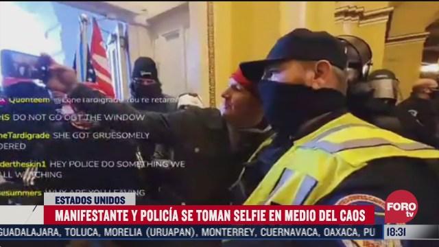 manifestante se toma selfie con un policia del capitolio