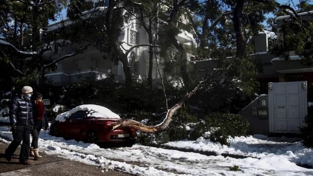 Una pareja camina por las calles de Grecia tras el temporal de frío y nieve