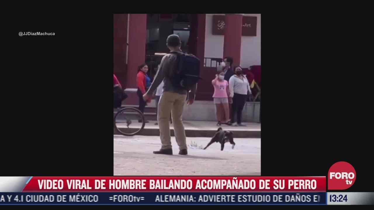 hombre baila con su perro en la via publica