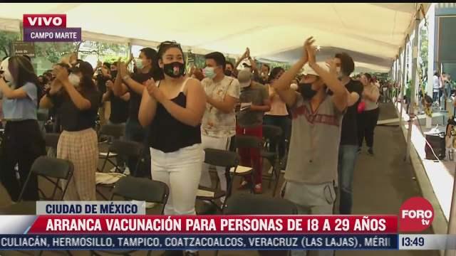 jovenes bailan y aplauden mientras esperan a ser vacunados contra covid 19 en cdmx