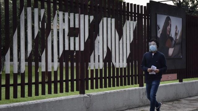 Un joven camina afuera de las instalaciones educativas del Instituto Politécnico Nacional (IPN)