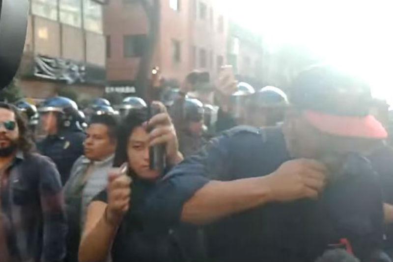 Mujer intenta quemar el rostro de un reportero durante marcha del 2 de octubre (video)
