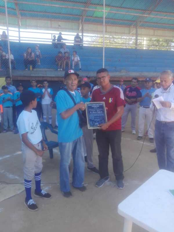 El legendario ex-lanzador y dirigente regional de Criollitos de Venezuela, Simón Infante, recibió placxa alegórica al homenaje.jpg
