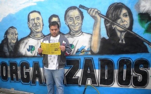 Marcos, militante de La Cámpora, dirige el centro cultural La Gloriosa, en Lanús (Buenos Aires). Aquí, leyendo NOTIRUYA frente al mural en la entrada al centro cultural