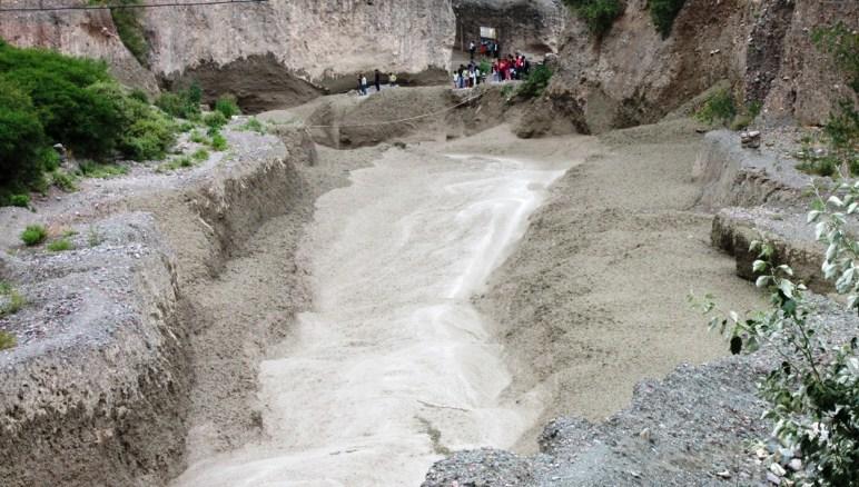 Como si fuera un torrente de lava, el volcán transcurre por el lecho del río Milmahuasi arrollando todo a su paso. Sobre la costa, se ve más gente congregada.