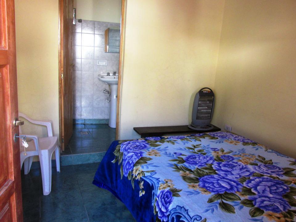 Habitación con cama matrimonial y baño privado.