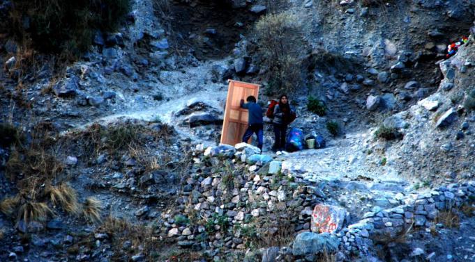 Descansando con una puerta. La mujer también carga. Más abajo, se ve un colchón. (Foto: Andrea Semplici).