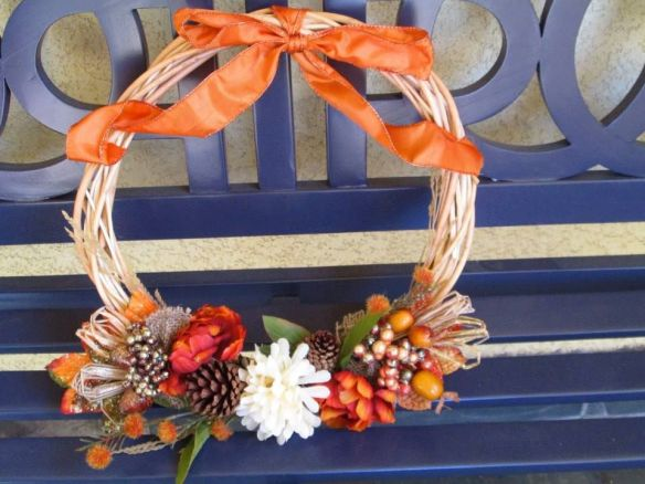 Flowers, berries, pinecones and ribbons dress this wreath up