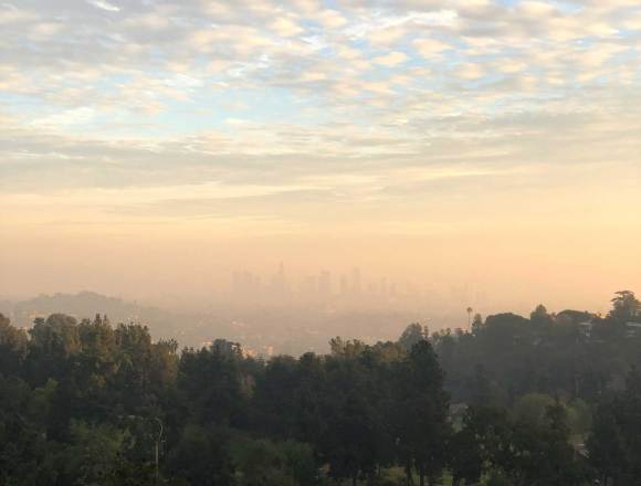 Picture of a foggy/smoggy sunset where you can barely make out a skyline of downtown Los Angeles