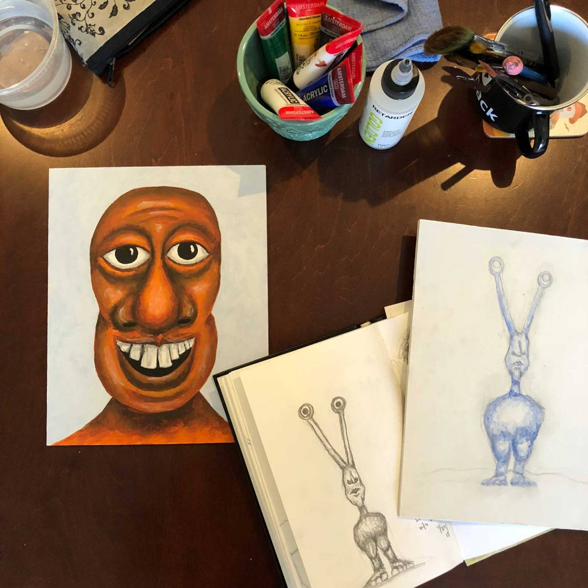 Finished orange monster portrait next to a painting in the beginning stages of a monster with weird antennae eyes and no arms