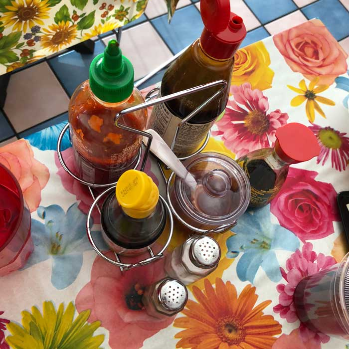 Photograph of pho condiments on a flowered table cloth