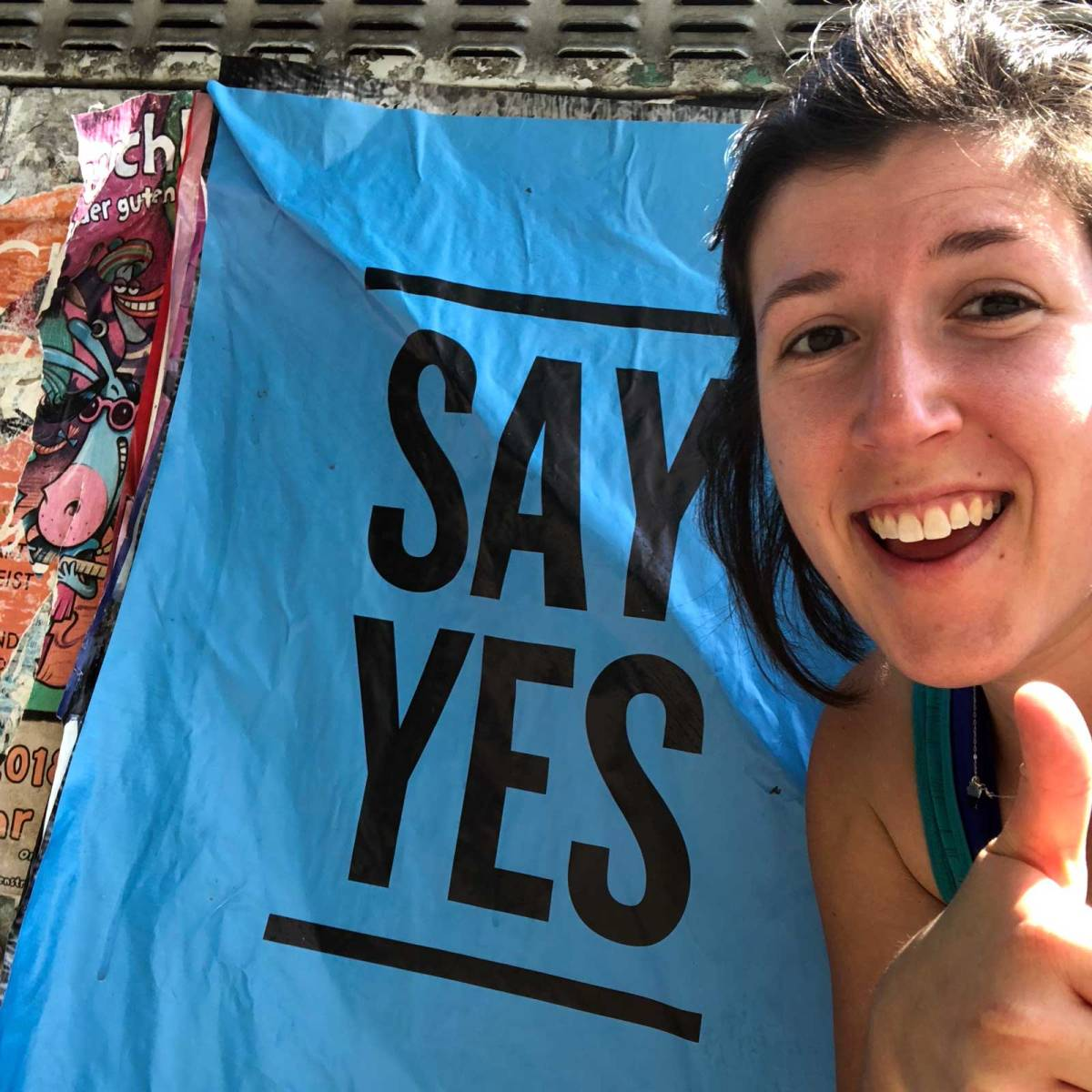"Lara posing with a thumbs up in front of a sign that says ""Say yes"""