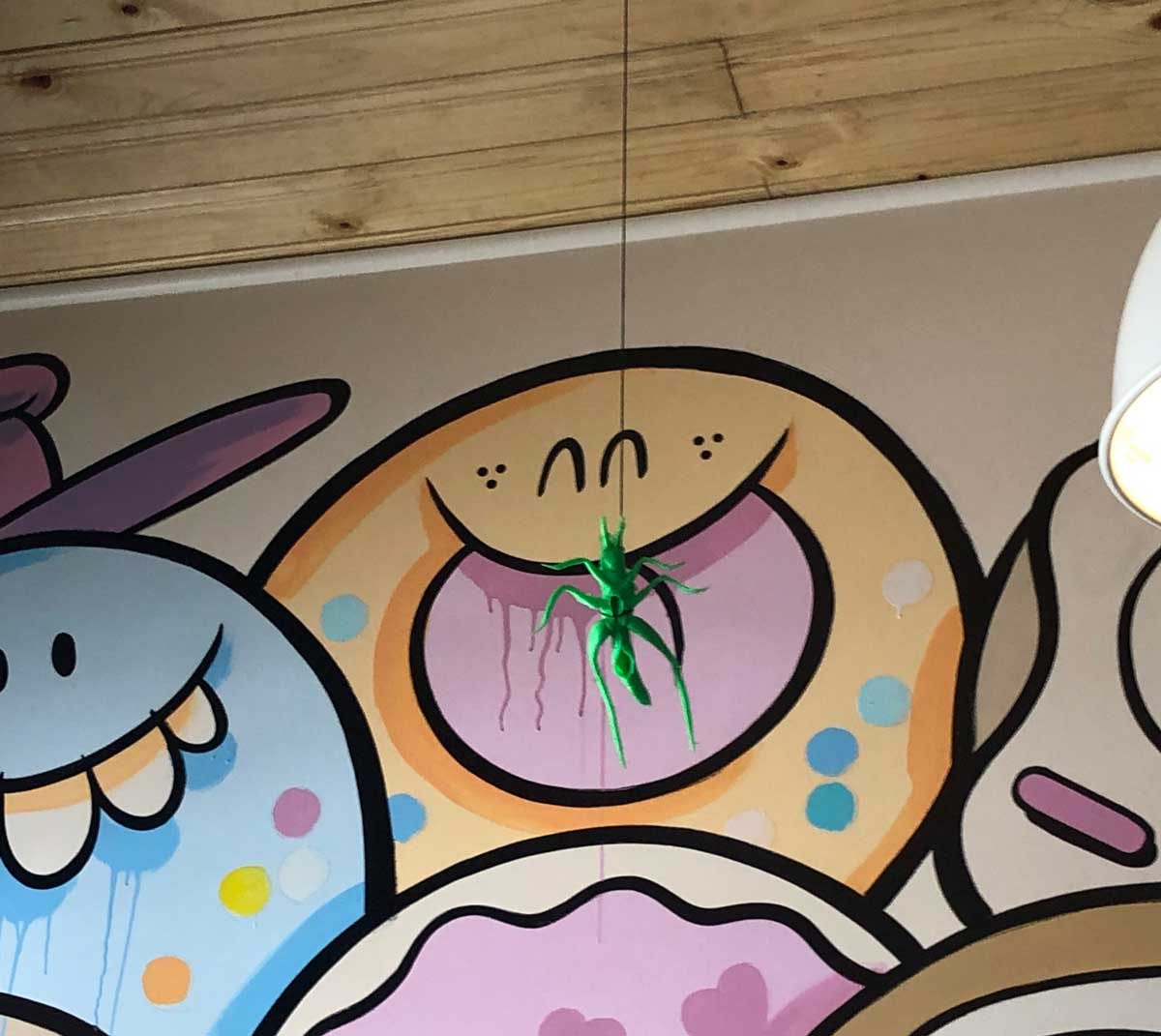A small toy grasshopper hanging from the ceiling in front of  a colorful mural