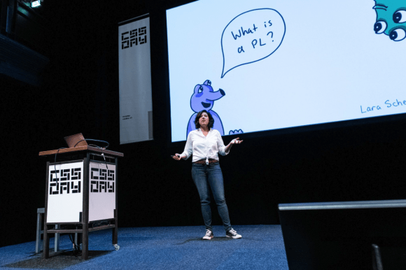 Lara presenting at a conference with a monster drawing in the background that says 'what is a PL'