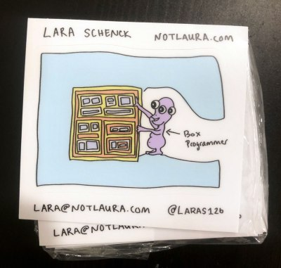 "Stickers containing an illustration of a monster doing a puzzle of boxes, and an arrow pointing to the monster saying ""Box Programmer"" and Lara's information"