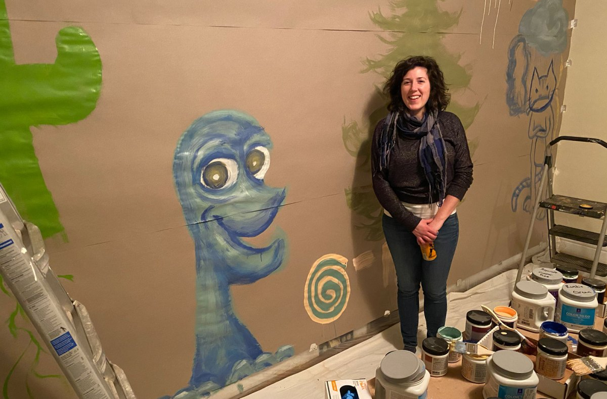 Lara posing with a blue monster she painted on brown paper attached to a wall