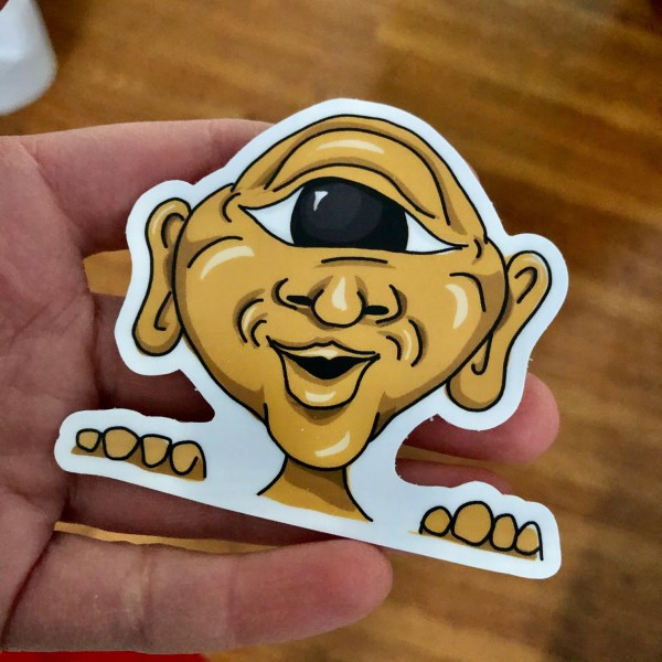A one-eyed, orange monster 3 inch sticker held in a hand