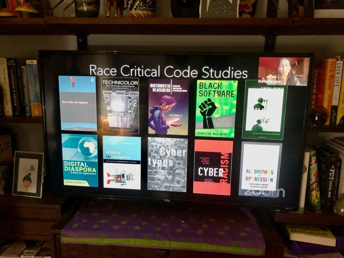 """Picture of a TV that has a slide reading """"Race Critical Code Studies"""" and 10 different book covers"""