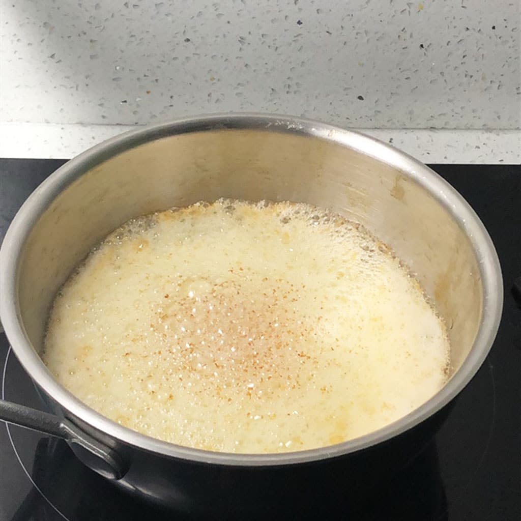 Foaming butter in saucepan with brown flecks on the surface of the foam, indicating brown butter is done.