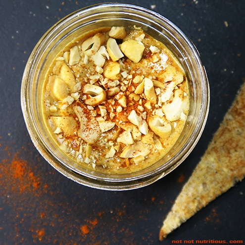 Top-down view of spicy cashew butter in a glass jar, against a dark background.