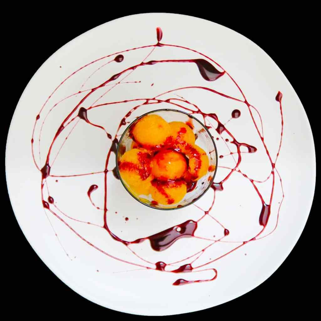 Papaya Ice in a small bowl, on a white plate drizzled with pomegranate reduction