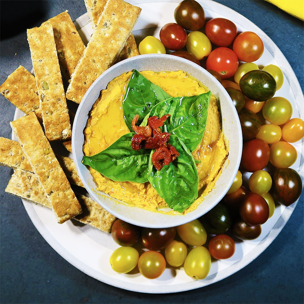 Top down view of 3-ingredient Sundried Tomato Hummus in a dish, surrounded by bread sticks and tomatoes.