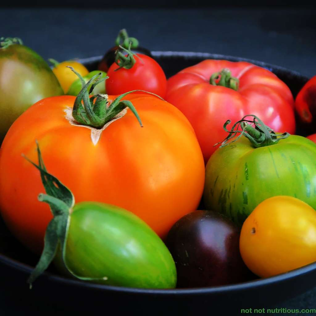 Black bowl with colourful Heirloom tomatoes, orange, green, red, yellow, and purple. The perfect tomatoes for Tomato and Bread Salad.