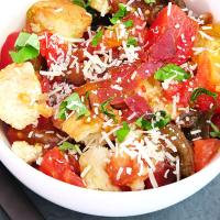 Topdown view of Tomato and Bread Salad, with fresh basil, and garlic. Bacon and cheese shown are optional ingredients.
