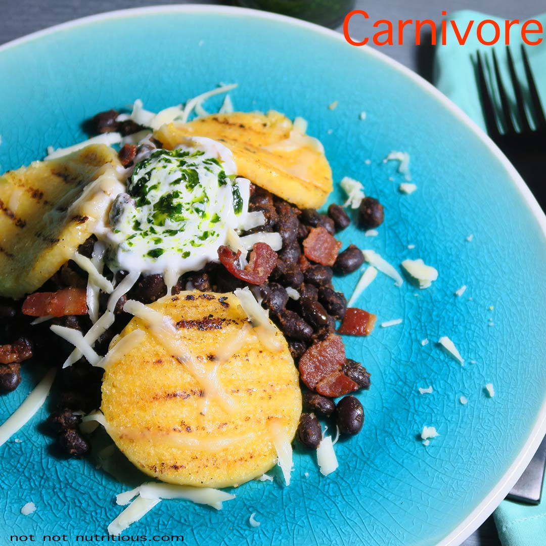 Blue plate with carnivore version of Black Beans and Polenta, with bacon, sour cream, and cilantro