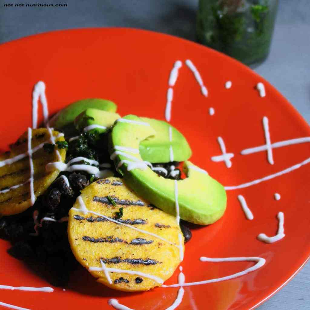 Pile of black beans, topped with grilled polenta rounds and avocado, on a bright red plate.