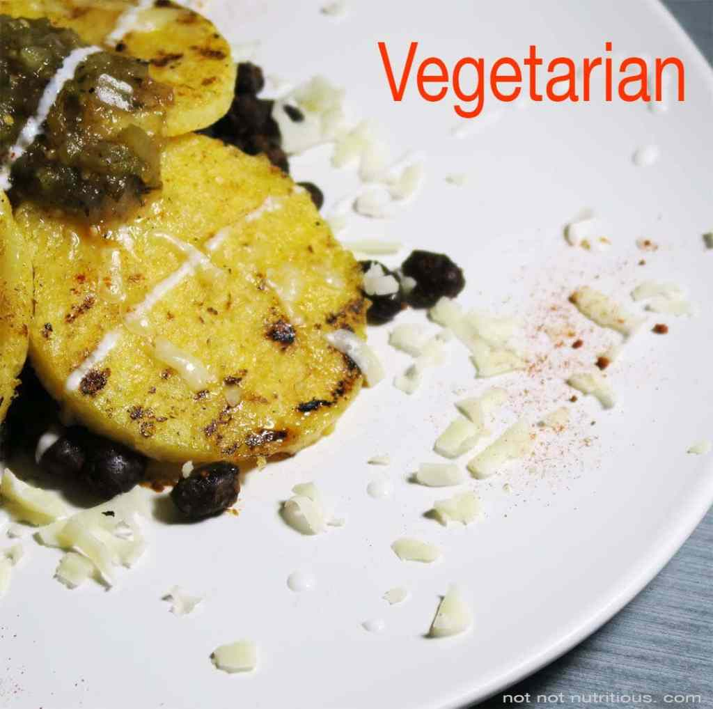 White plate with vegetarian version of Black Beans and Polenta, with cheese and sour cream