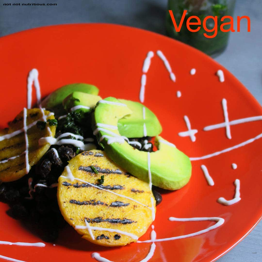 Orange plate with vegan version of Black Beans and Polenta, with avocado slices and vegan sour cream