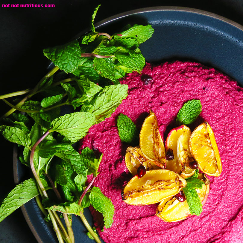 Top down view of Beautiful Beet Hummus with Harissa, Lemon, and Pomegranate Seeds, on a black plate.