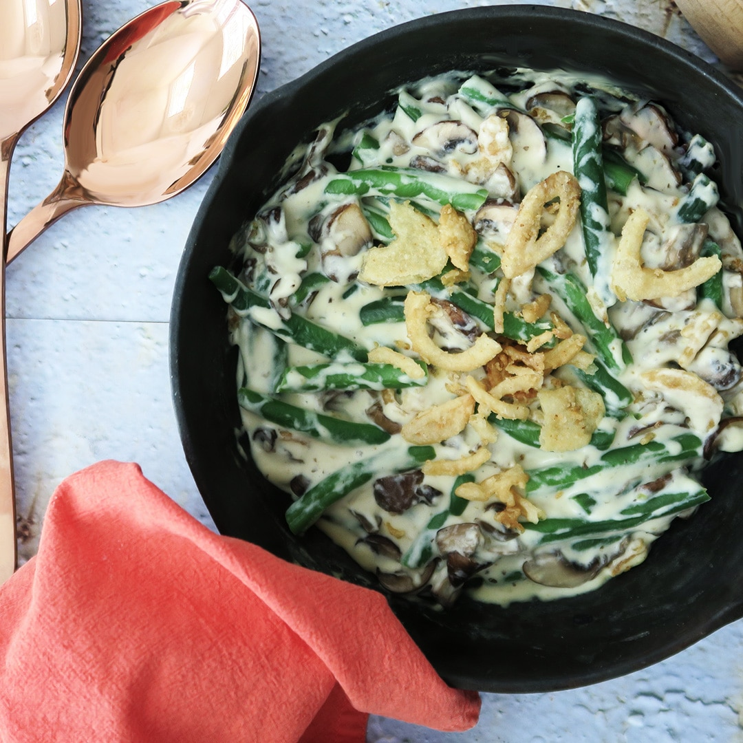 A vegan green bean casserole in a skillet, showing green beans, cream sauce, mushrooms, and crispy fried onions.