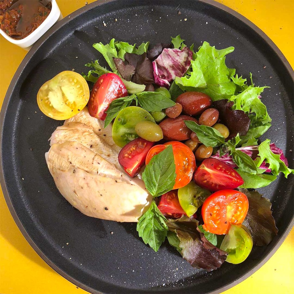Mediterranean Salad featuring chicken breast, colourful tomatoes, different coloured olives, greens, and fresh basil, all on a black plate