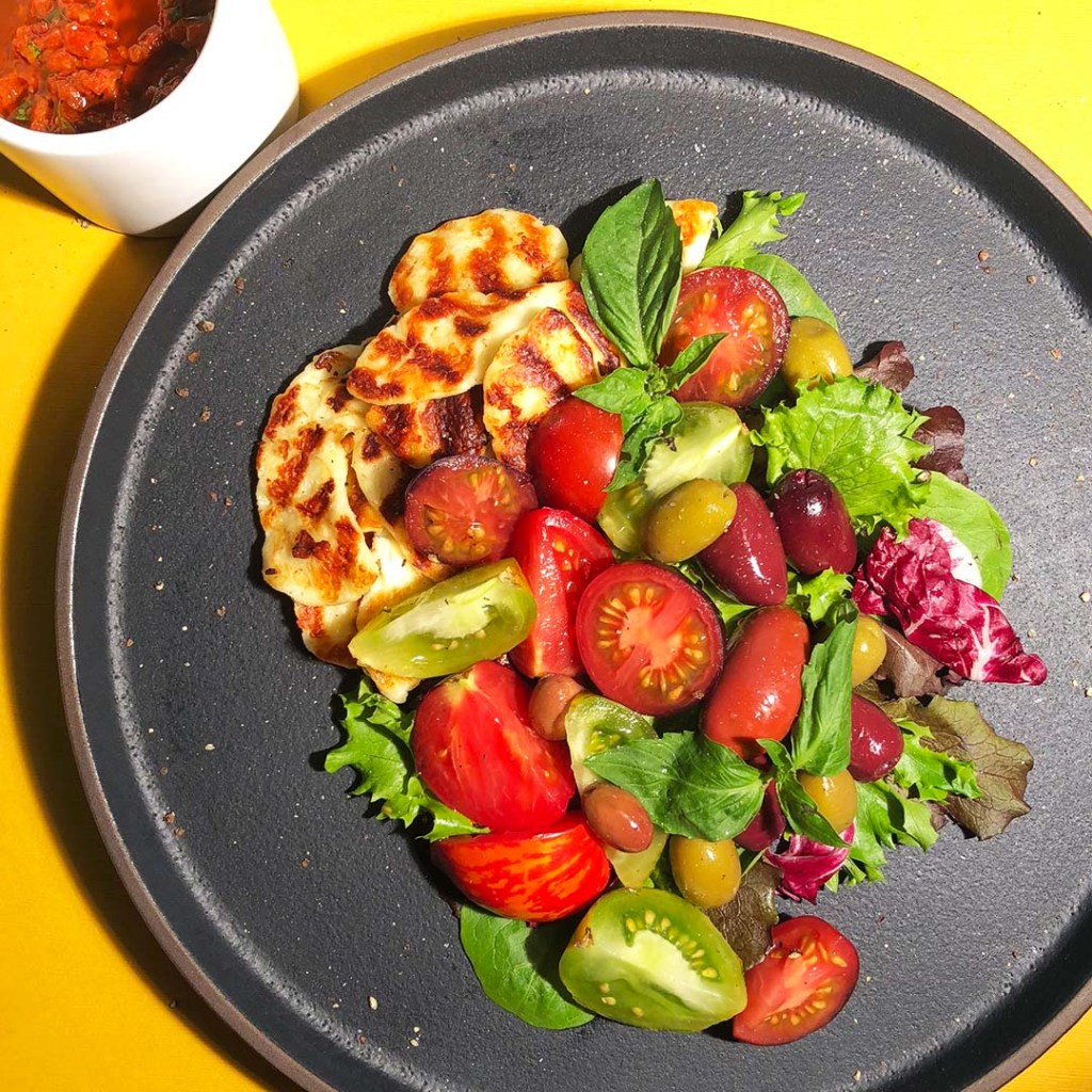Mediterranean Salad featuring halloumi cheese, colourful tomatoes, different coloured olives, greens, and fresh basil, all on a black plate
