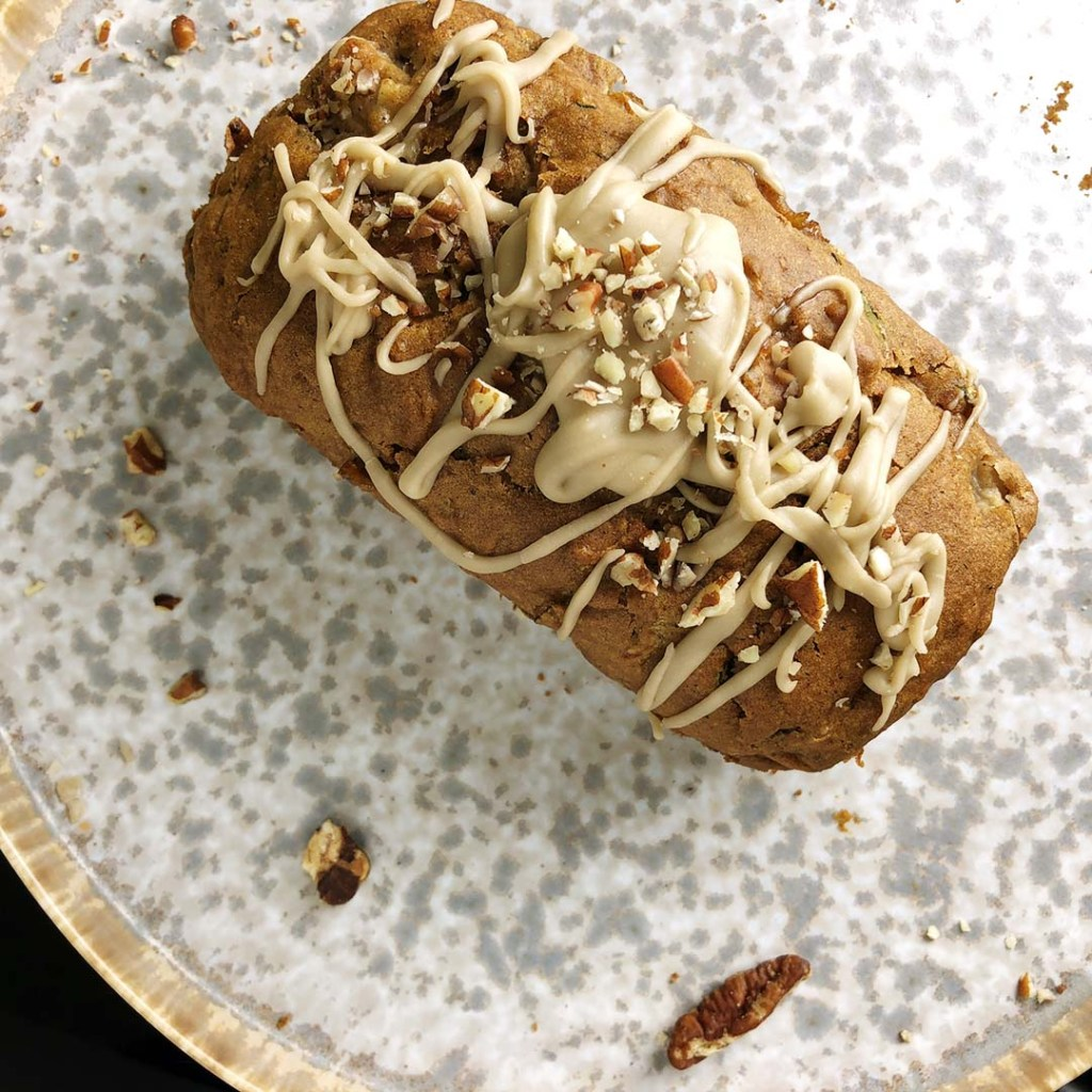 Top down shot of pear zucchini loaf drizzled with vanilla pecan glaze