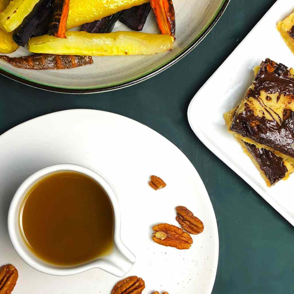 Pitcher of vegan brown butter on a white plate with pecans. In the background are roasted carrots and chocolate chip cookie bars, both made with brown butter.