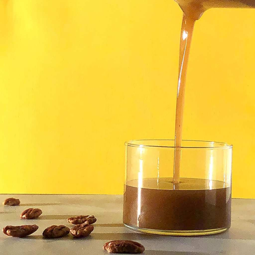 Easy vegan brown butter being poured into a glass container, against a yellow background, with pecans scattered nearby