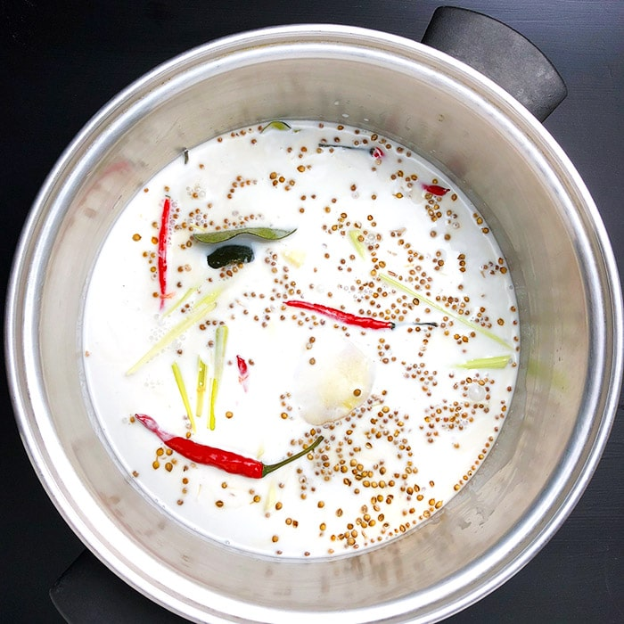 Coconut milk and emongrass, ginger, coriander, lime, and Thai chilis in a large saucepan