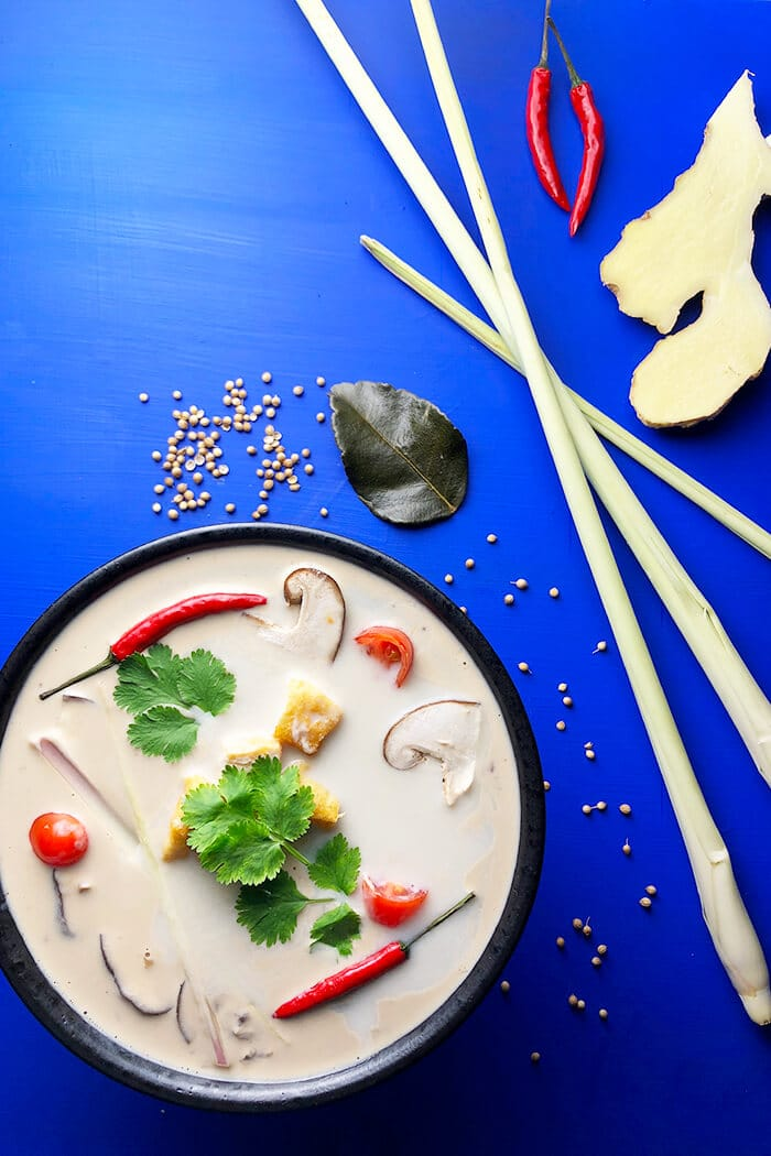 Tom Kha Soup with tofu puffs in a black bowl on a bright blue background with coriander, lemongrass, ginger, and lime leaves.