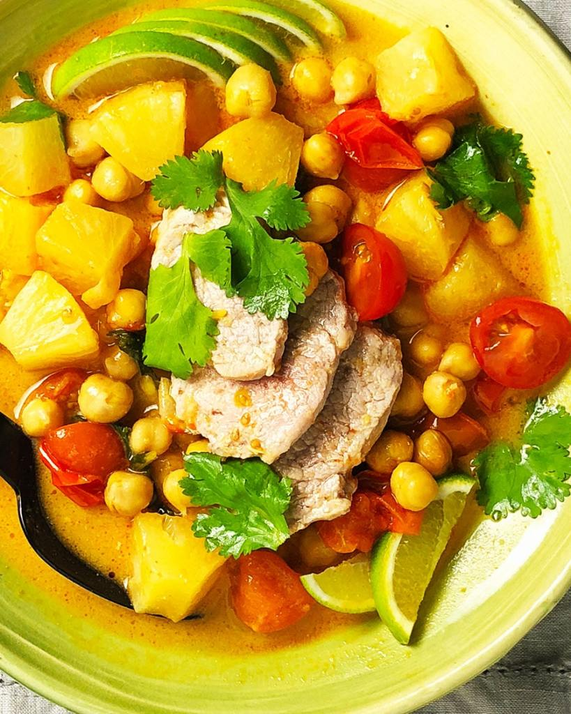 A close-up, topdown view of a bowl of Thai Chickpea Curry with Pork, containing red curry paste, coconut milk, chickpeas, tomatoes, pineapple, and seasonings.