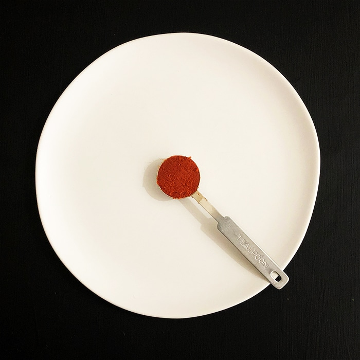 A top-down view of a teaspoon of red curry paste on a white plate against a black background. Ingredient in 15-minute Thai Chickpea Curry