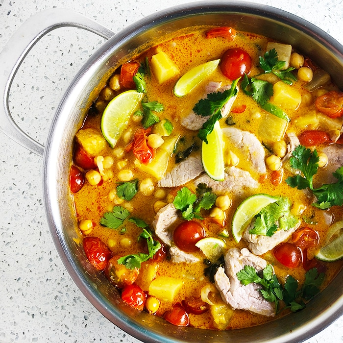 Top-down view of 15-minute Thai Chickpea Curry in a frying pan. Curry features chickpeas, red curry paste, coconut milk, pineapple, tomatoes, cilantro. Pork is optional.