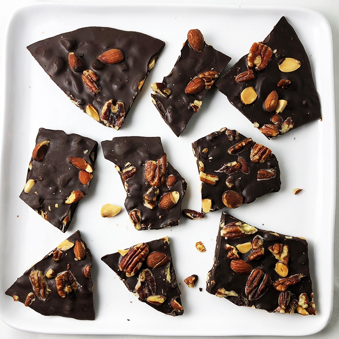 Top-down view of dark chocolate bark studded with buttery pecans and smoked almonds, on a square white plate.