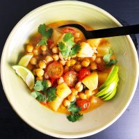 A topdown view of a bowl of Thai Chickpea Curry, containing red curry paste, coconut milk, chickpeas, tomatoes, pineapple, and seasonings.