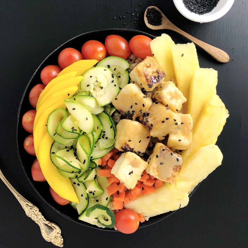 A top-down shot of a Buddha Bowl containing tomatoes, mango, zucchini, carrots, pineapple, and tofu, topped with Pineapple Brown Butter Teriyaki Sauce and sprinkled with black sesame seeds. All on a black background with a small wooden spoon with black sesame seeds.