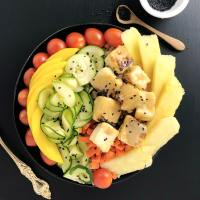 Top down view of Buddha Bowl with Pineapple Brown Butter Teriyaki Sauce on Salty Crispy Tofu, with cherry tomatoes, mango, raw zucchini, carrots, and pineapple.