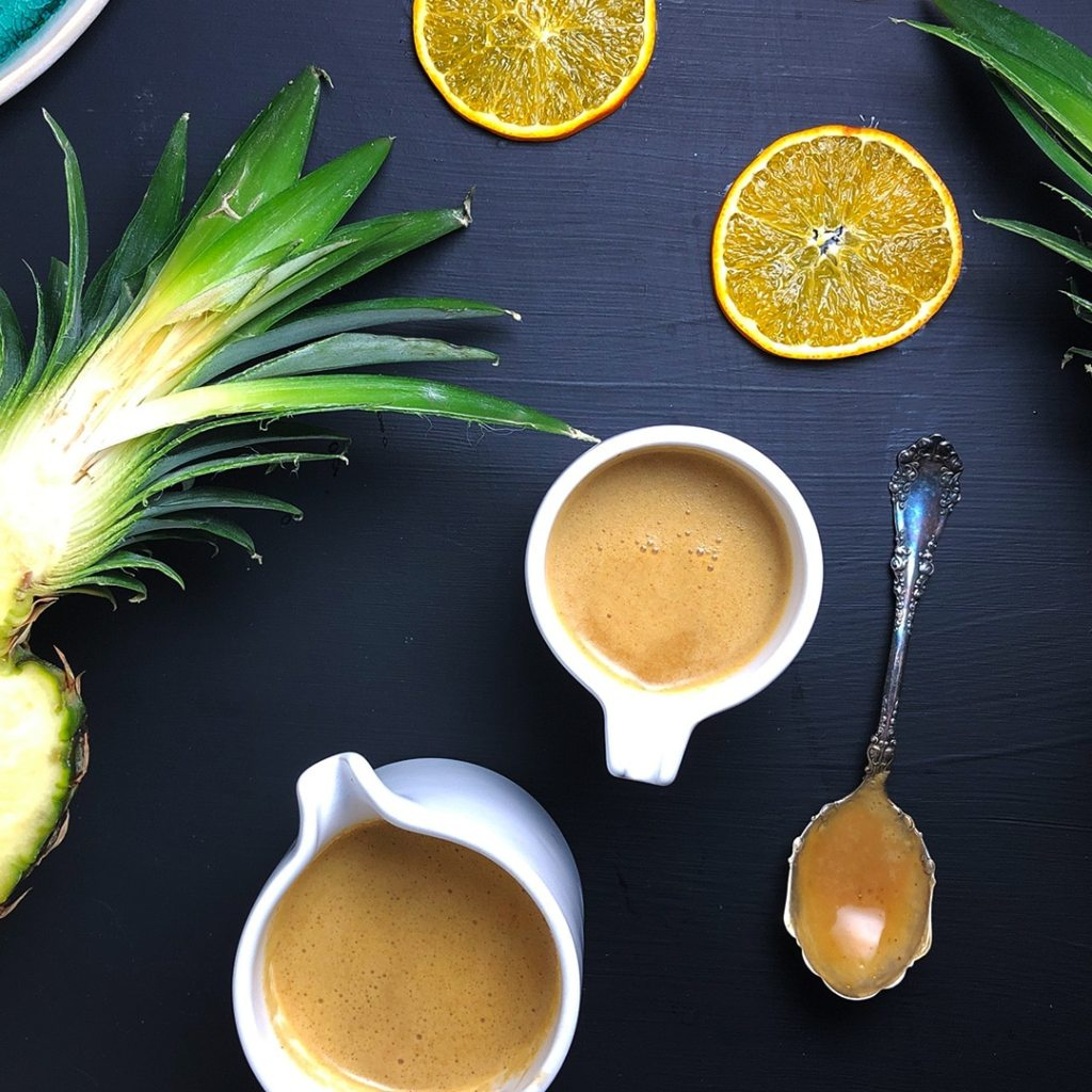 Top down view of two white vessels of Pineapple Brown Butter Teriyaki Sauce, alongside a spoon with some sauce, orange slices, and a halved pineapple, all against a black background.