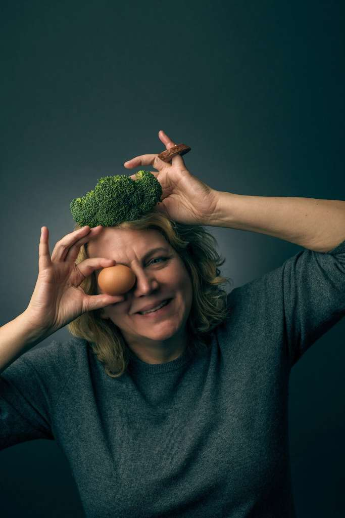 A headshot of notnotnutritious site owner, Sylvia Eastman, with a crown made of broccoli, an egg monocle, and a pinky ring made from kielbasa sausage. Representing the eating together made easy theme of the recipe site.
